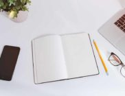 White work table with notes, smartphone and laptop